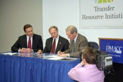 photo of Ron Troyer with DMACC and Grand View presidents signing agreement