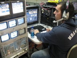 photo of Eric Michel directing scoreboard crew at men's basketball game