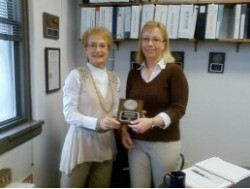 Mary Jo Smith, left, hands the Meritorious Service Award to Kristi Fuller.
