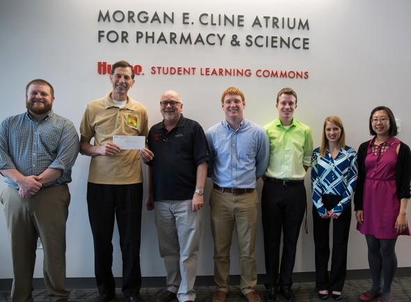 Professor John Rovers, third from left, and Drake students deliver a $4,700 check to Medicine for Mali President Dave Merschman, second from left, on May 8.