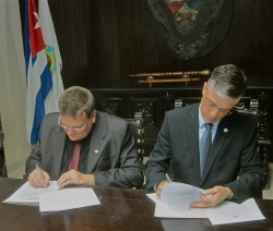 Drake University President Marty Martin (right) and University of Havana Rector Gustavo Cobreiro Suárez sign the memorandum of agreement on December 10.