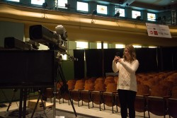 Samantha Ohlson photographs the set of the Iowa Brown and Black Presidential Forum in Sheslow Auditorium, where the three Democratic presidential candidates would later take the stage.