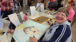 Mara, a person supported by the local nonprofit group Mosaic, shows off an artistic work-in-progress.