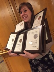 Katie Bandurski, a sophomore Magazine Media major, poses with Drake's university-wide and individual Pacemaker awards.
