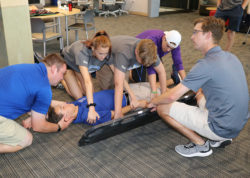 Students attempting a spine board transfer in AT lab